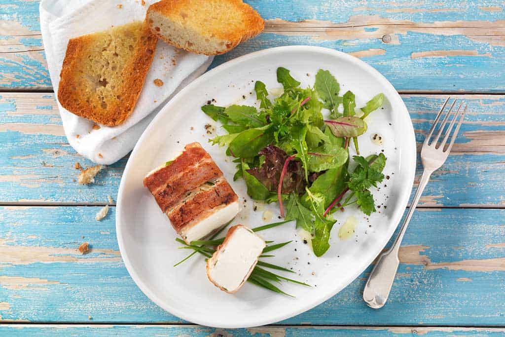 Fetakäse im Bacon-Mantel mit Weizengras.